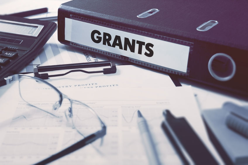 44385116 - grants - office folder on background of working table with stationery, glasses, reports. business concept on blurred background. toned image.