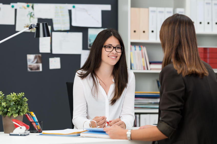 31843658 - two young businesswomen having a meeting in the office sitting at a desk having a discussion with focus to a young woman wearing glasses
