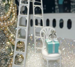 The iconic Tiffany blue gift box surrounded by jewels in the window of the Tiffany & Co. New York City store, Dec. 26, 2016 (Photo by Robert Fitzpatrick) Creative Commons license via Flickr