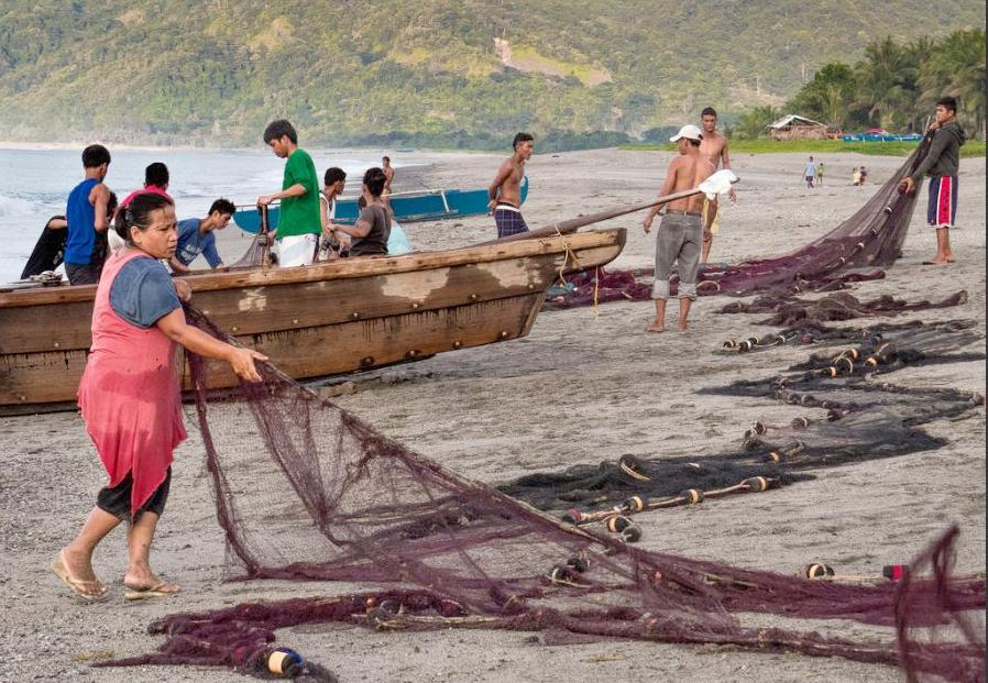 Members of a fishing village in Pagudpud, Philippines untangle and prepare their fishing nets for late evening fishing off shore to catch small tuna. May 2015 (Photo by Wayne S. Grazio) Creative Commons license via Flickr
