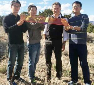 Los Alamos Center for Advanced Solar Photophysics researchers hold a large prototype solar window. From left: Jaehoon Lim, Kaifeng Wu, Victor Klimov, Hongbo Li. Photo courtesy Los Alamos National Laboratory) Public domain