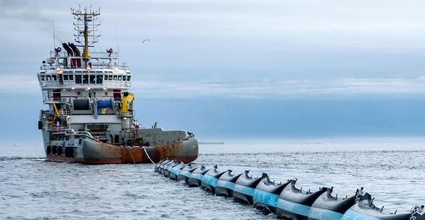 Ship tows The Ocean Cleanup's 2016 prototype plastic collector into the North Sea for testing. (Photo courtesy The Ocean Cleanup)