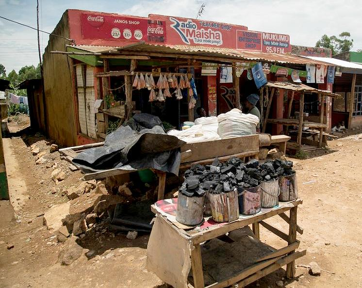 Businesses sell cans of charcoal for cooking at a market near Kisumu, Kenya, March 11, 2015. (Photo by Peter Kapuscinski / World Bank)