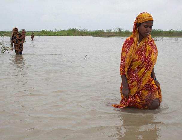 Climate Displacement in Bangladesh: The Jamuna River has swollen from heavier than usual monsoon rainfall causing severe flooding on the islands. Women on Dakkin Patil Bariare are forced to wade across waterlogged land. August 2011 (Photo by Stuart Matthews) Creative Commons license via Flickr