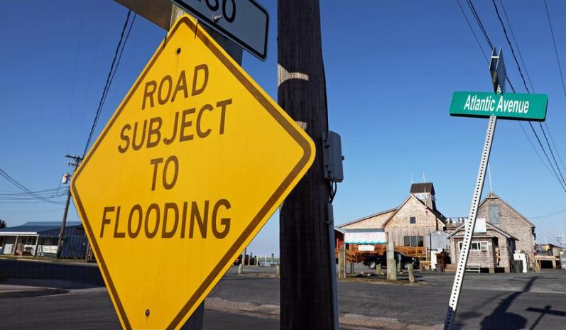Road sign warns of flooding in Wachapreague, Virginia on Tuesday, July 10, 2018. (Photo by Aileen Devlin / Virginia Sea Grant) Creative Commons license via Flickr