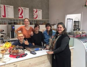 The first customer to shop at waste-free NADA Cafe, East Vancouver, Canada. Founder Brianne Miller, center, in black. October 22, 2018 (Photo courtesy NADA) Posted for media use.