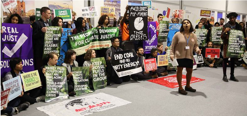"Participants in a civil society action organized by Corporate Accountability International call for ambition and equity at COP24, presenting the ""People's Demands for Climate Justice."" Dec. 4, 2018, Katowice, Poland (Photo courtesy Earth Negotiations Bulletin) Used with permission."