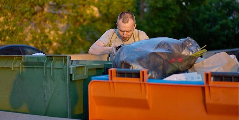 Man digs through garbage bins in Moscow, Russia, June 23, 2016 (Photo by Vladimir Buynevich) Creative Commons license via Flickr