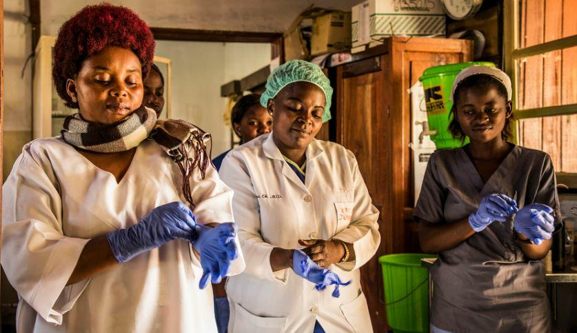 Health workers put their gloves on before checking Ebola patients at the hospital in Beni, Democratic Republic of Congo, January 16, 2019 (Photo by Vincent Tremeau courtesy World Bank) Creative Commons license via Flickr.