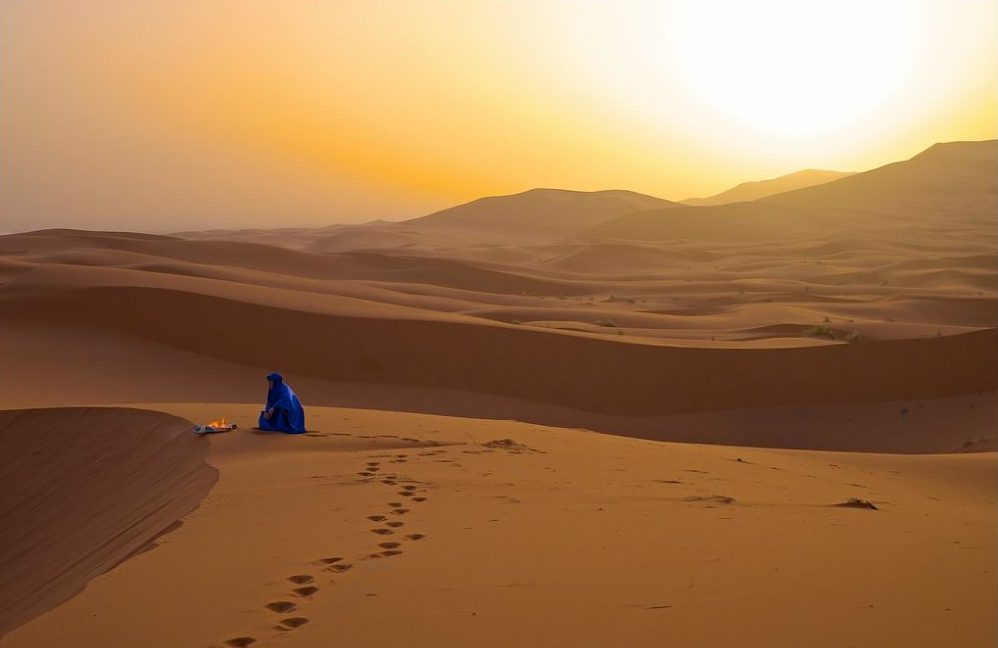 A Bedouin man rises with the Sun in the Sahara Desert, Morocco. April 14, 2015 (Photo by Jamie McCaffrey) Creative Commons license via Flickr.