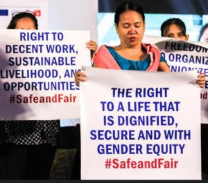 A group of women leads the Migrants/Women Workers Oath to protect, promote and defend their rights as women, as workers, and as migrants. They held placards to highlight the core rights and principles of their oath. The Philippines, April 16, 2019 (Photo by ILO Asia and the Pacific)