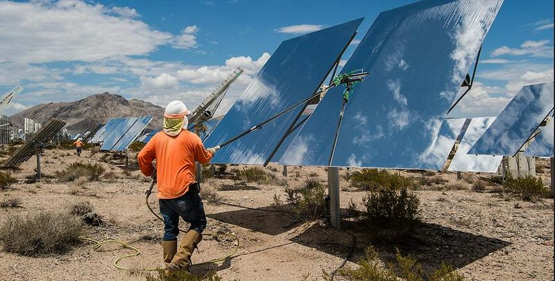 Contracted workers clean heliostats at the Ivanpah Solar Project, a concentrating solar power facility in California's Mojave Desert. Over 300,000 software-controlled mirrors track the sun in two dimensions and reflect the sunlight to boilers that sit atop three 459 foot tall power towers. July 26, 2017, Nipton, California. (Photo courtesy National Renewable Energy Lab) Public domain