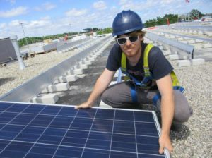 Installer with one of more than 3,600 solar panels being installed in Oakville, Ontario, Canada. July 23, 2015 (Photo by Rob Campbell) Creative Commons license via Flickr