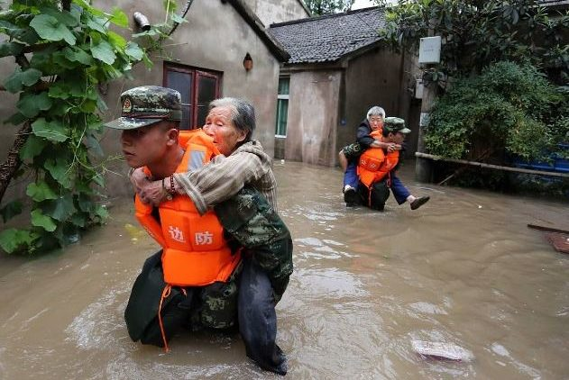 Chinese paramilitary policemen rescue elderly people trapped in their homes by flooding rains that left 112 dead and affected 16 million people near the Yangtze, China's longest river. July 2016, Nanjing, China (Photo courtesy Sino-German Urbanisation Partnership) Public domain.