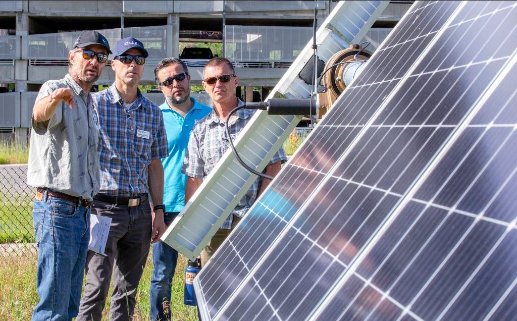 U.S. National Renewable Energy Lab (NREL) research technician Otto Van Geet (left) gives a tour of the Photovoltaic Central Array Testing Site to participants in NREL's Executive Energy Leadership Academy, June 20, 2019 (Photo by Werner Slocum / NREL)