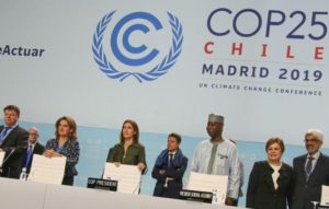 Dignitaries gather at the podium for the opening ceremony of the COP25 high-level segment. Front row second from left, Teresa Ribera, Minister for the Ecological Transition, Spain; Carolina Schmidt, COP25 President, Minister of the Environment, Chile; Tijjani Muhammad-Bande, President, UN General Assembly; Patricia Espinosa, Executive Director UN Climate Change, December 11, 2019 Madrid, Spain (Photo courtesy Earth Negotiations Bulletin)