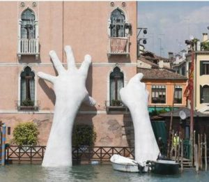 "A smaller version of Lorenzo Quinn's monumental sculpture ""Support"" was on display at the United Nations Climate Change Conference COP25 in Madrid to remind participants of rising sea levels that threaten Venice and all coastal cities. The installation, shown here, was first unveiled by Quinn at the Venice Biennale in 2017. Two gigantic hands of a child emerge from the Grand Canal in Venice to protect and support a historical building threatened by climate-induced flooding. Given the 50-year-record floods that hit Venice this month, Quinn's alert is more urgent than ever. 2019 (Photo courtesy UNFCCC)"