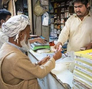 Azeem, 27, at his shop in Karachi, Pakistan. Afghan refugees like Azeem have recently been allowed to open bank accounts. 2019 (Photo by Roger Arnold courtesy UNHCR)