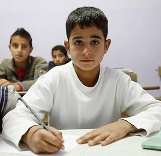 """This boy from Syria was 11-years-old at the time of this picture in 2013. He was living with his family in a makeshift tent shelter in Lebanon's Bekaa Valley. He hadn't been to school for two years because of the conflict, but then he was granted two hours of schooling every day. """"The best thing about being back at school is that I can study again,"""" he said. """"I want to be a doctor when I'm older, and I really like to study and learn."""" (Photo courtesy UK Dept. of International Development) Creative Commons license via Flickr"""