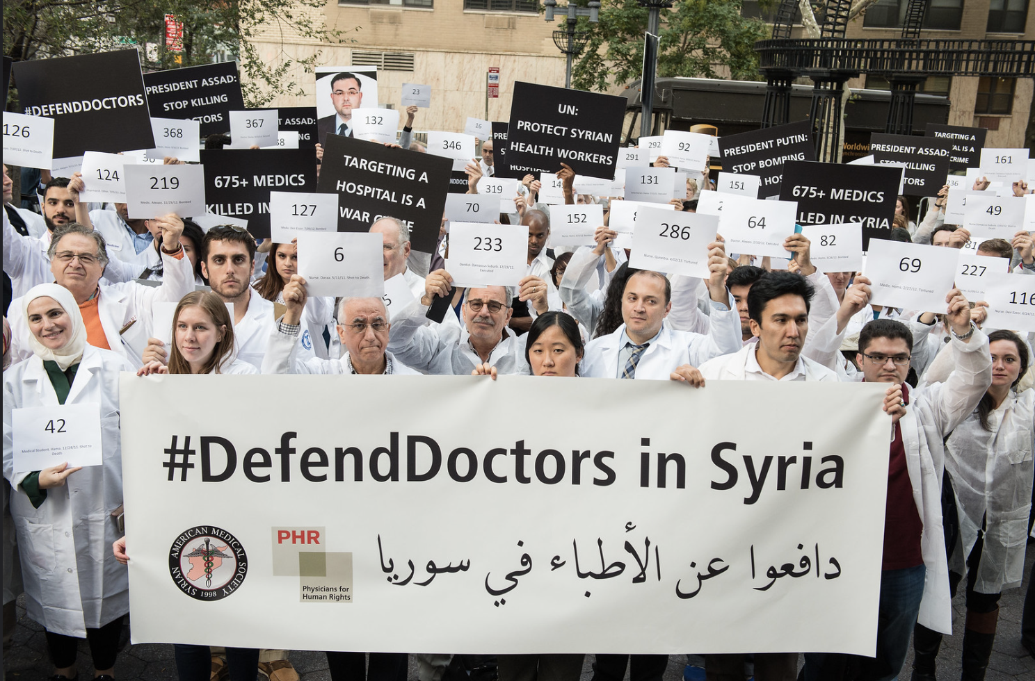 Caption: Medical personnel have been demanding protection for doctors in Syria for years, now this protection is critical to keep the deadly coronavirus from spreading. Here, supporters demand an end to the bombing of hospitals in Syria at a die-in to defend Syrian health professionals, November 4, 2015 (Photo by Michael Hnatov courtesy Physicians for Human Rights) Creative Commons license via Flickr