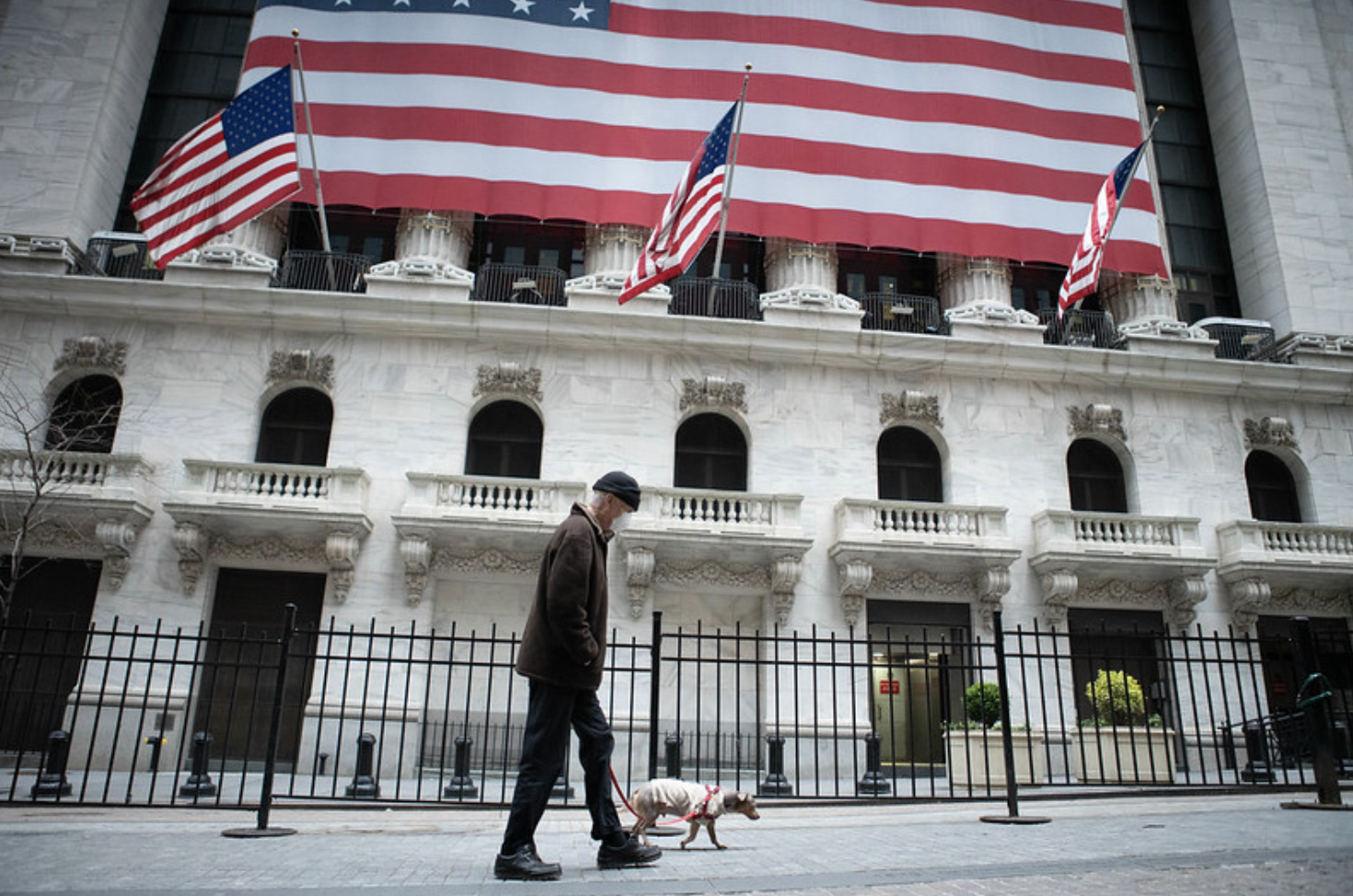 Man in a mask to prevent spread of the coronavirus walks his dog in front of the New York Stock Exchange, where the floor is closed to traders due to the virus. April 12, 2020 (Photo by Anthony Quintano) Creative Commons license via Flickr