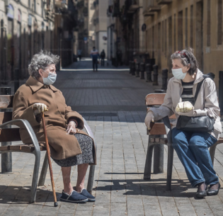 Mother and daughter maintain social distancing and wear protective masks as they share time in the spring sunshine, May 3, 2020, Barcelona, Spain (Photo by Fotomovimiento) Creative Commons license via Flickr