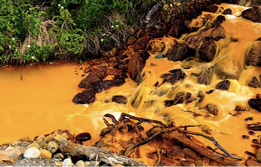 Acid mine drainage turns the water orange near the Tulsequa River, in northwestern British Columbia, Canada, 2018 (Photo courtesy U.S. Geological Survey) public domain