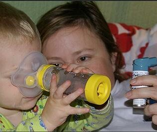 A mother shows her 32- month-old boy his first asthma inhaler. This inhaler was not designed by pupils in the Cambridge University study. May 31, 2007 (Photo by Thomas Widmann) Creative Commons license via Flickr