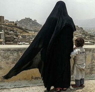 An internally displaced Yemeni woman and her daughter look over the capital city of Sana'a, Yemen. August 2017 (Photo by Giles Clarke courtesy UN Office for the Coordination of Humanitarian Affairs) Posted for media use