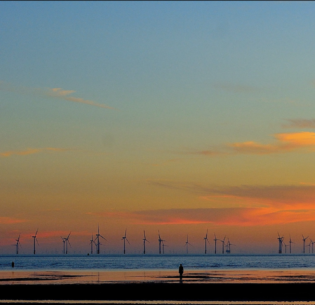 A wind farm offshore of Crosby Beach,Liverpool, Merseyside, England at sunset. June 18, 2017 (Photo by Tee Cee) Creative Commons license via Flickr