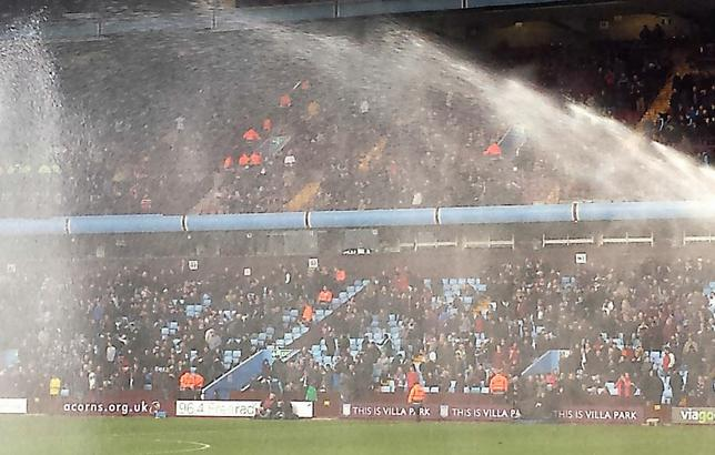 Villa Park is a football stadium in Aston, Birmingham, England. Ground staff water the football pitch to make the surface fast and slick. November 9, 2013 (Photo by John Garghan) Creative Commons license via Flickr