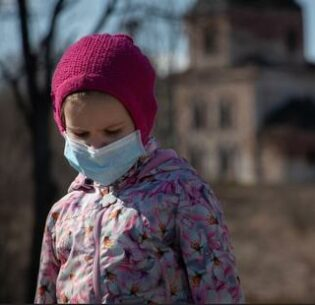 Young girl in France, saddened by the COVID-19 pandemic, wears a facemask to protect herself and others from the deadly virus. April 5, 2020 (Photo by Nik Anderson) Creative Commons license via Flickr