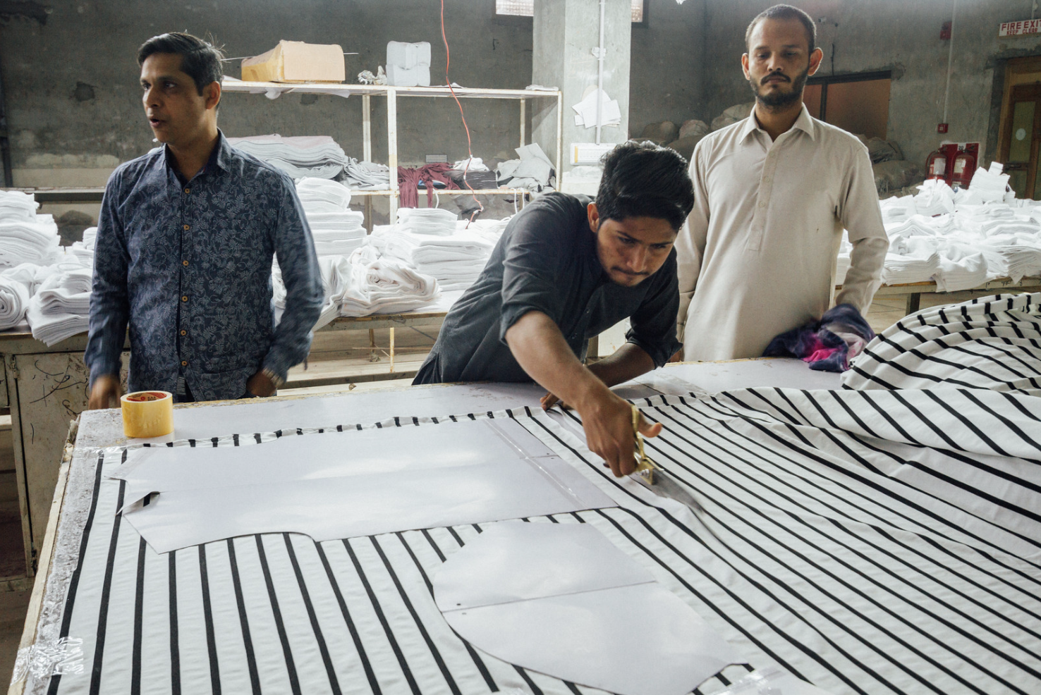 Garment workers cut cloth to pattern sizes at a clothing factory in Faisalabad, Punjab, Pakistan, March 3, 2020 (Photo by Adam Cohn) Creative Commons license via Flickr