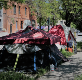 Homeless people camping on the sidewalk in Denver, Colorado, June 3, 2021 (Photo by Daniel Moskowitz) Creative Commons license via Flickr)
